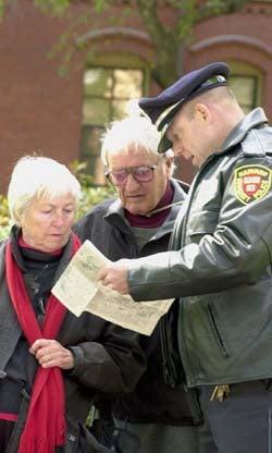 Charles Marren helps tourists in Harvard Yard