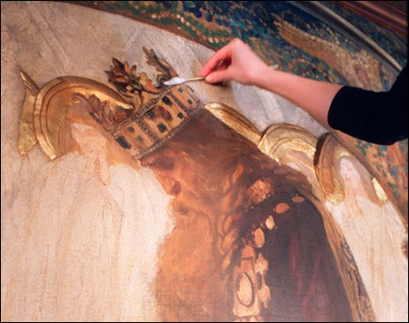 mural being cleaned with giant cotton swab