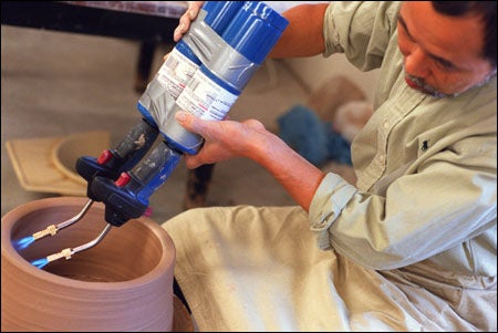 applying blowtorches to a pot