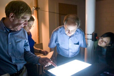 (Cambridge, MA - June 25, 2009) – From left, Josh Grindlay, Paine Professor of Practical Astronomy, Alison Doane, Curator of Plate Stacks, Edward Los, Software Engineer, and Sumin Tang, Research Assistant in Astronomy give a tour of the Plate Stacks scanning room inside the Center for Astrophysics at Harvard University. As part of the CFA DASCH project, thousands of glass plates from the last century of observation are being scanned to make them more accessible to modern scholars.Photo Kris Snibbe/Harvard University News Office