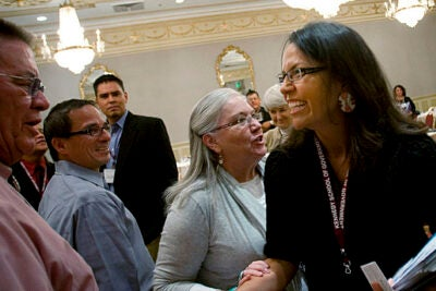 Jodi Archambault Gillette, deputy associate director of intergovernmental affairs in the Obama administration (right), meets with attendees after her talk. American Indians have a voice in the White House and the attention of the new president, she told the group.