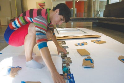 Carlin Wing '02 assembles her exhibit at the Carpenter Center.