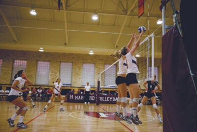 Two Crimson players go up for the block in Harvard's 3-2 loss to UConn.