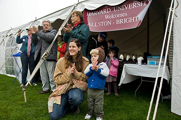 Birgit Swain and 22-month-old Elliot Swain of Brighton applaud the Harvard Band during the Allston-Brighton pre-game festivities.