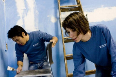 Joseph Lai '14 and Iulia Cojocarv '11 don blue Harvard public service T-shirts while painting over the blue rooms of the Cambridge Community Center.