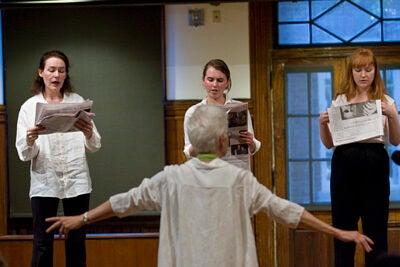 """Alison Knowles (back to camera), a Radcliffe Fellow this year, offers an example of Fluxus with a performance of """"Newspaper Music,"""" a simultaneous reading out loud with Knowles """"conducting."""""""