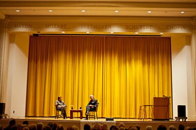 Former New York Times reporter Linda Greenhouse, now a member of Harvard's Board of Overseers (left), moderates a talk with President Drew Faust (right) before an audience of Harvard alumni at Paine Hall.