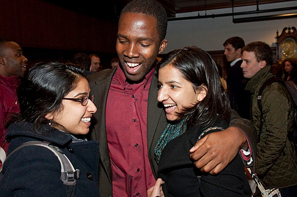 Nworah Ayogu, first marshal of the Class of 2010 (center), gets a hug of mutual congratulations from Rashmi Jasrasaria '10 (left), and and Jyoti Jasrasaria '12 following the midyear graduation ceremony, which was held in the Radcliffe Gymnasium.