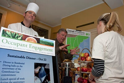 Chef Brian Corcoran (left) and Harvard Dining Services buyer John Aiken staff the local foods table during a green fair at Dudley House in December.
