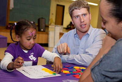 Kindergartener Denise Brito (left) and her mother Dina Goncalves (right) get help from HASI's Brandon Due.