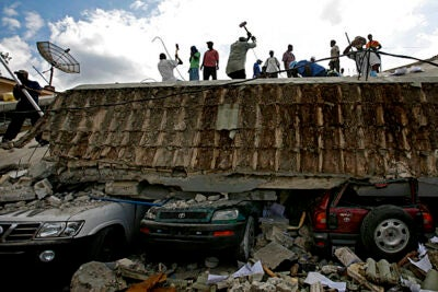 People search for survivors under the rubble of a collapsed building after an earthquake hit Port-au-Prince, Haiti. Groups of experts and medical personnel affiliated with Harvard University, which has several institutional ties to the country, have mobilized to assist the devastated region.
