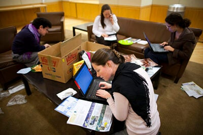 "Volunteers from the Office for Sustainability collect unwanted mail in collection areas around the campus.  Eco-citizens Sage Kochavi (clockwise from left), Montana Higo, Dara Olmsted, and Claire Reardon participate in a ""junk mail party"" to unsubscribe people from companies' mailing lists."