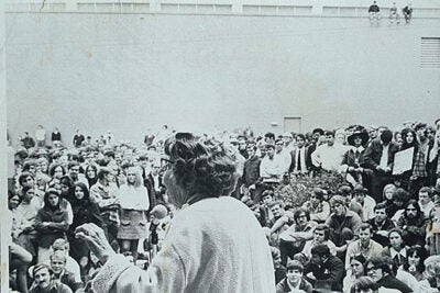 1970: Jeannette Rankin, standing behind a microphone, addressing a large group of University of Georgia students (including three people seated on a university building roof).
