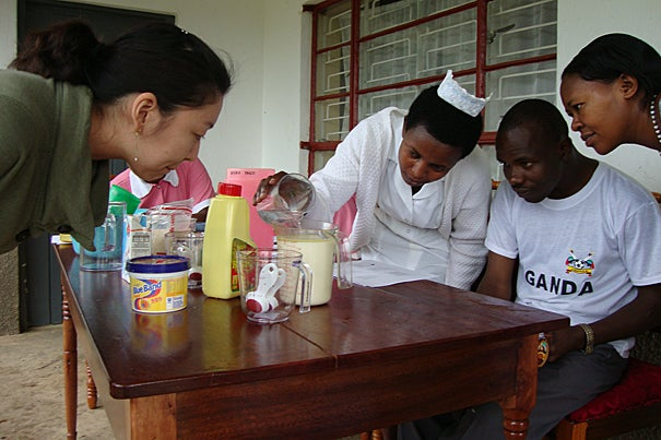 In Uganda, Sarah Nam (left) teaches how to make high-energy milk for nutritional therapy for the malnourished.