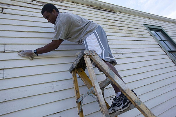 "Former Crimson running back Clifton Dawson '07 joined other Harvard alumni as he worked with the Phillips Brooks House Association during its Alternative Spring Break program. Painting a shotgun-style house the size of a rail car, Dawson said,  ""It's a small house, but it's a big job."""