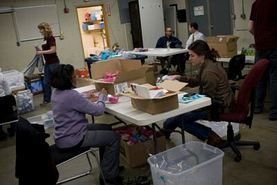 Harvard Public Affairs and Communications staff members turn stacks of math and language arts games into 1,800 SmartTALK learning kits in a warehouse near HASI's Allston headquarters.