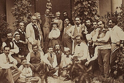"From the Artistic Space section: Harriet Goodhue Hosmer Papers, 1852–1972, photograph of Hosmer surrounded by her Italian workmen, 1861. The photograph shows Hosmer — elfin, pugnacious, and defiant — in the center of a group of rough male artisans in Italy. On the back, the inscription reads, ""Hosmer and Her Men."""