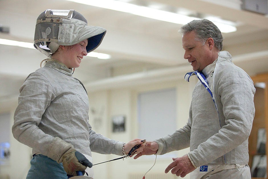 Caroline Vloka '12 works up a sweat and gets some tips from fencing coach Peter Brand.  Kris Snibbe/Harvard Staff Photographer
