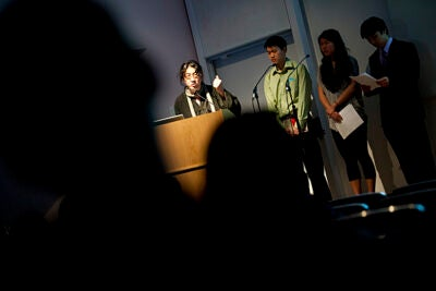 "Editors of three literary magazines banned or at risk in their home countries talk about the hard work of creative writing in oppressive regimes. ""The Living Magazine"" event that takes place in the Sackler Museum auditorium features a panel of writers from China, Iran, and Burma. Bei Ling (left) speaks from the podium."