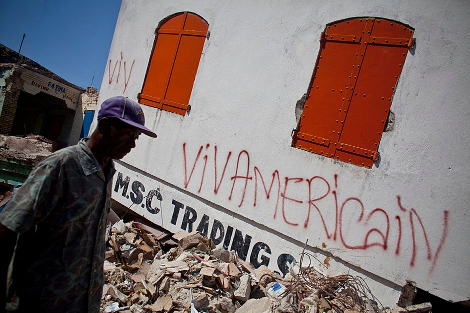 A man walks by graffiti scrawled upon the wall of a destroyed building.    Justin Ide/Harvard Staff Photographer
