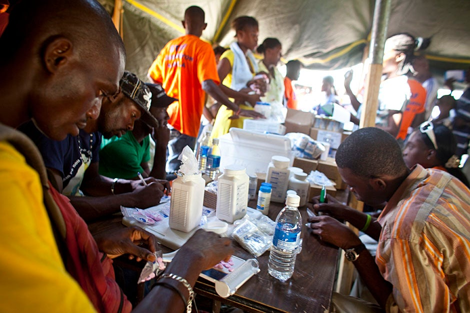Employees and volunteers from Partners In Health distribute medicine at a mobile health clinic within a camp for internally displaced persons that holds about 45,000 people.  Justin Ide/Harvard Staff Photographer
