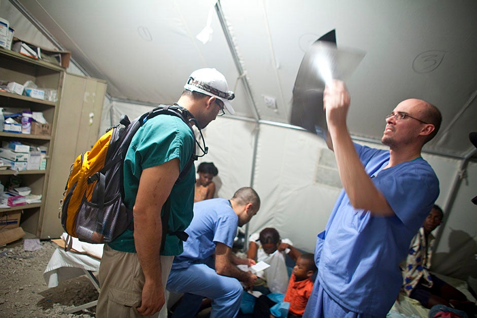 Sharam Aarabi (center), a student at the Harvard School of Public Health, and Jason Smithers (right) from Children's Hospital Boston are two of many helping out.   Justin Ide/Harvard Staff Photographer