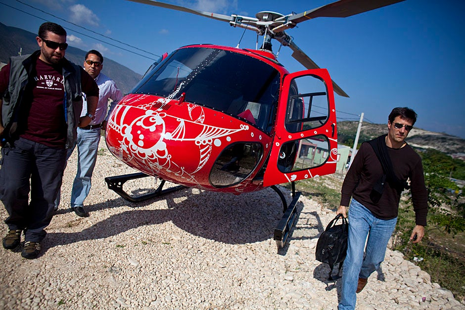 Alejandro Baez (left), a former student at the Harvard School of Public Health, and Michael VanRooyen of the Harvard Humanitarian Initiative exit a helicopter for a meeting with the vice president of the Dominican Republic.    Justin Ide/Harvard Staff Photographer