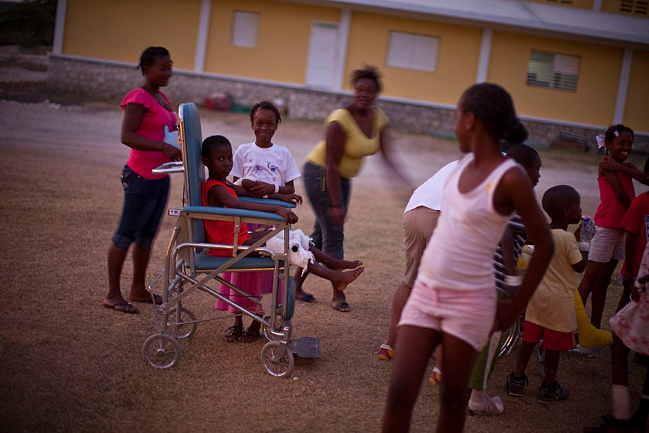 Children play outside the triage tent at the rehabilitation hospital in Fond Parisien, Haiti.    Justin Ide/Harvard Staff Photographer