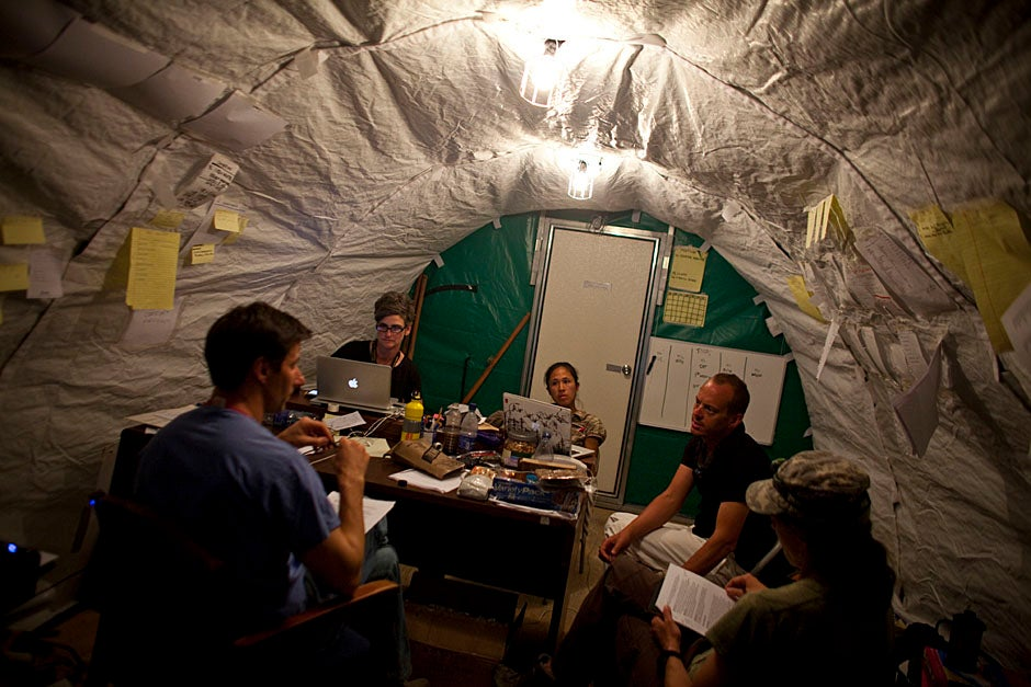 At Fond Parisien, Haiti, Michael VanRooyen (from left), Hilarie Cranmer, Jennifer Chan, Christian Theodosis, and Emilie discuss the needs of the camp and how to get funding for their relief work. Justin Ide/Harvard Staff Photographer