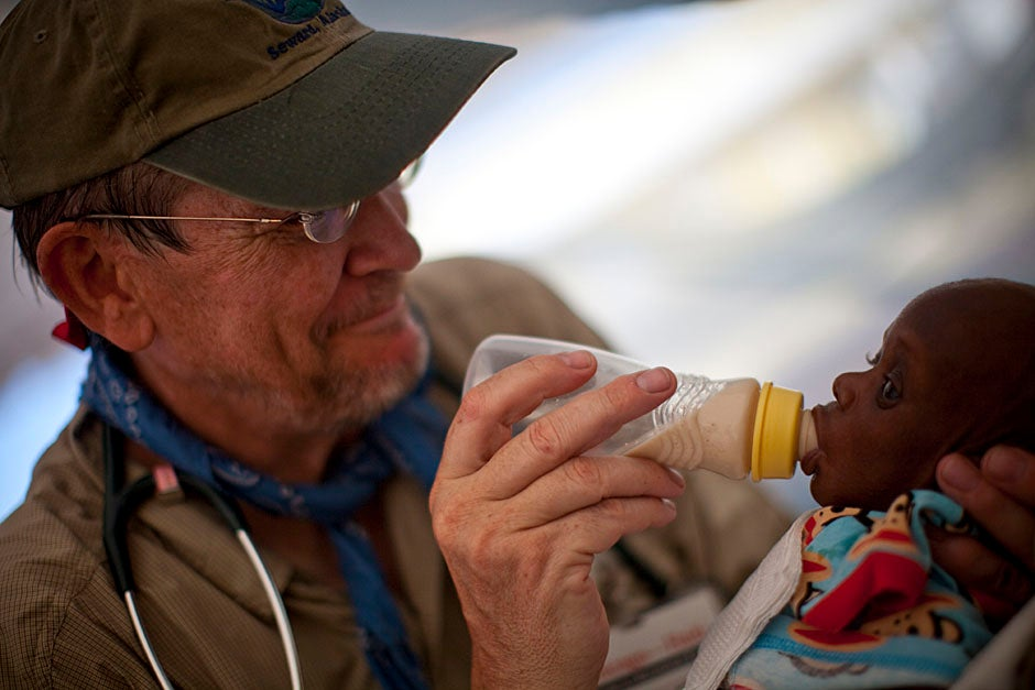 Richard Cook of the University of Chicago works with Yyolson Eliassaint, a young boy suffering from malnutrition due to the loss of his mother and the inability to find food in the capital.    Justin Ide/Harvard Staff Photographer