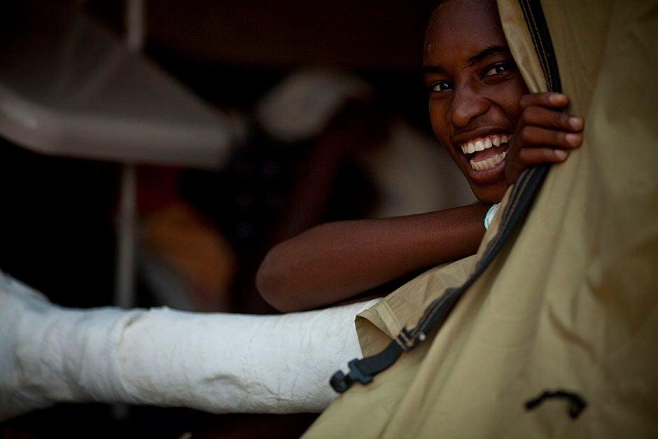 A young boy with a crushed left leg hides behind a tent and smiles.   Justin Ide/Harvard Staff Photographer