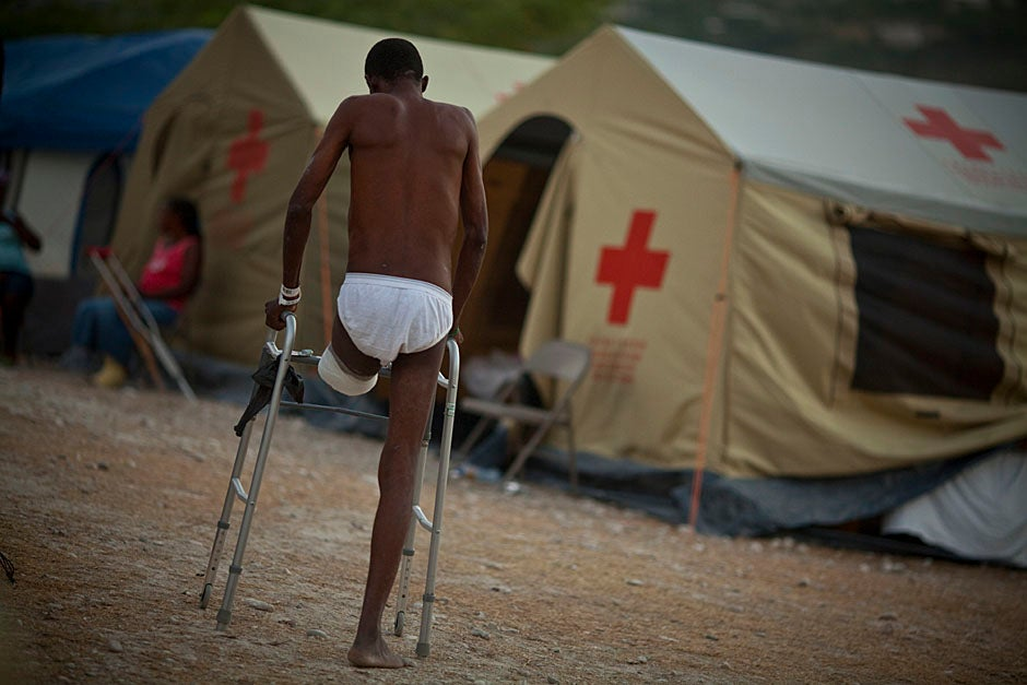 A man who had his left leg amputated makes his way through the camp.   Justin Ide/Harvard Staff Photographer