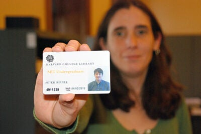 HCL assistant head of library billing and privileges Ann-Marie Costa displays a sample library pass, which will give MIT undergraduates access to HCL libraries.