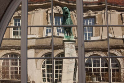 Views of a lion statue reflected in mirrored windows at the Center for European Studies.