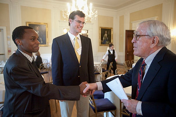 David Mbau '13 (left), who will be interning in Johannesburg, and Elihu Reynolds '12, who will intern in London, meet with Paul Weissman '52 during the spring luncheon.