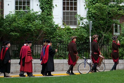 Kirkland House graduates and other regalia march along Holyoke Street toward Harvard Yard in the early morning.