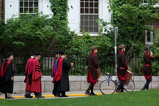 Kirkland House graduates and other regalia march along Holyoke Street toward Harvard Yard in the early morning.