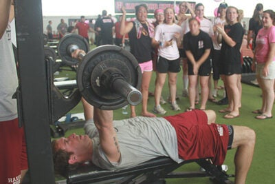In the Bench Press for Breast Cancer, freshman Tom Rubel represents the men's lacrosse team while members of the athletic community offer encouragement.