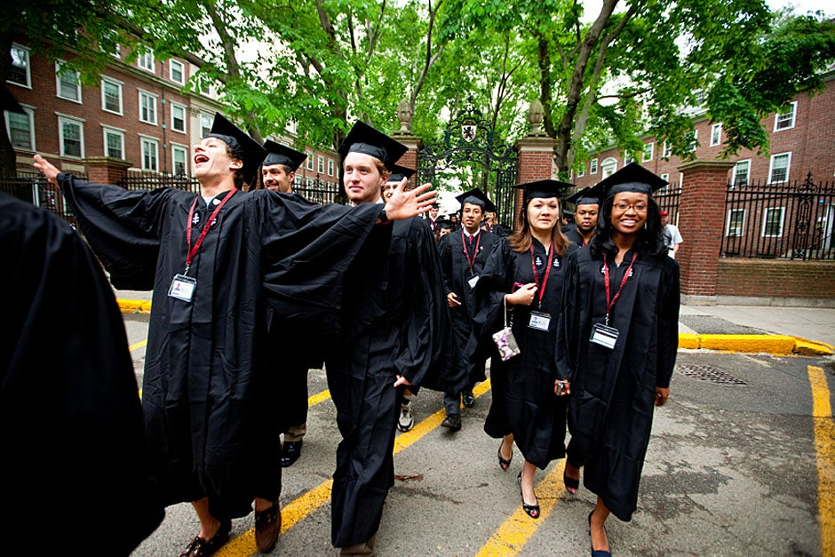 Winthrop House graduates Jonathan Steinman (from left), Laura Peterzan, and Laurel Macey march up Dunster Street toward Commencement Exercises. Rose Lincoln /Harvard Staff Photographer