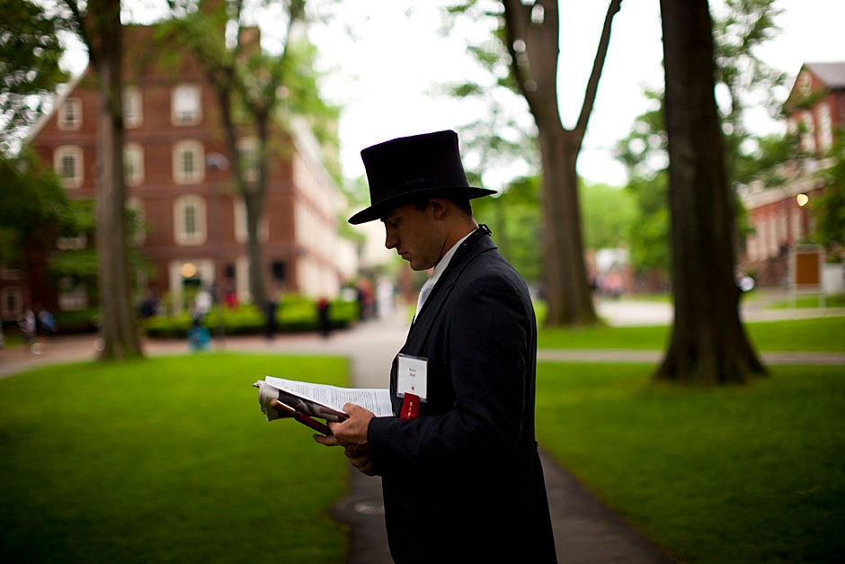 Marshal Aaron Byrd reads in the yard before the exercises begin. Stephanie Mitchell/Harvard Staff Photographer