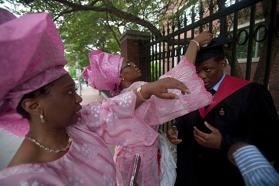 Yinka Adio (from left) and Abimbola Odutayo help Kayode Odutayo of the Harvard School of Public Health straighten his cap and gown. Kris Snibbe/Harvard Staff Photographer