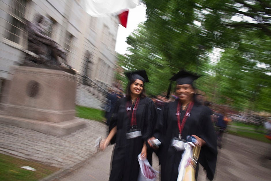Graduates from the College pass the John Harvard Statue and University Hall on their way to the senior service. Justin Ide/Harvard Staff Photographer