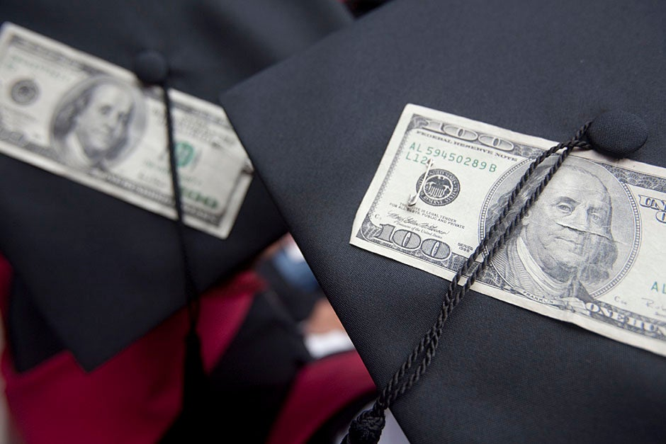 Harvard Business School graduates wear hundred dollar bills pinned to their caps in celebration of Commencement. Kris Snibbe/Harvard Staff Photographer