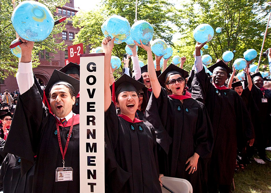 Mohammad Chishti (left) and Katherine Chon celebrate the conferral of their degrees with Harvard Kennedy School classmates. Jon Chase/Harvard Staff Photographer
