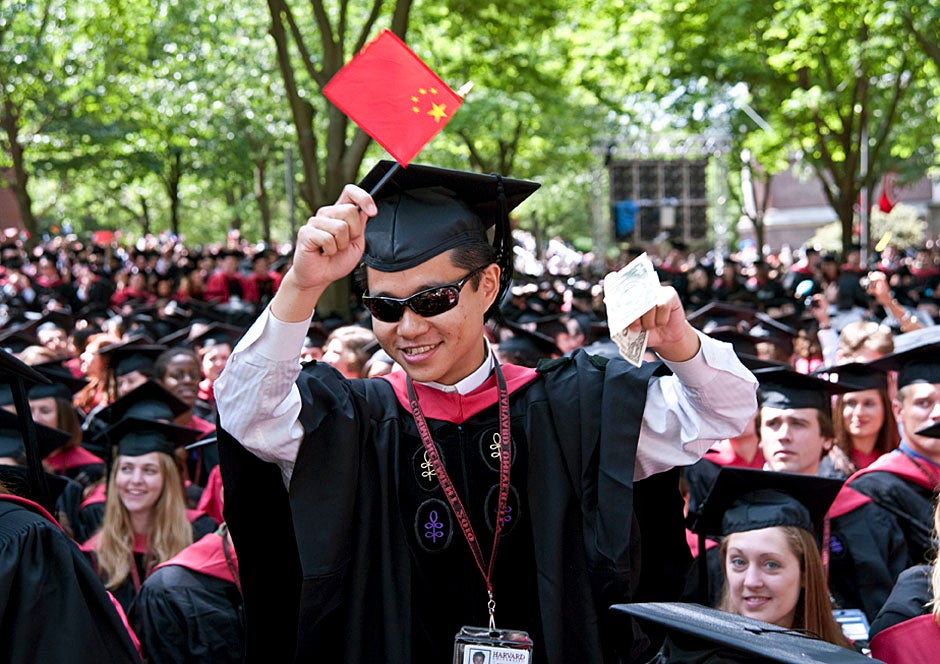 Harvard Business School graduate Tong Chen celebrates by waving a dollar bill and the Chinese flag. Jon Chase/Harvard Staff Photographer