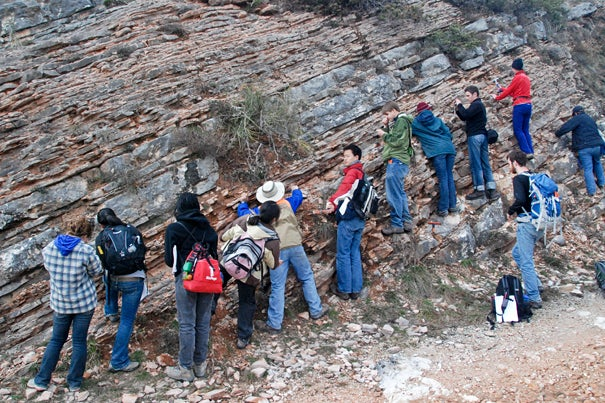 Students (below) line up along the boundary rock layer, which marks the mass extinction that killed the dinosaurs.