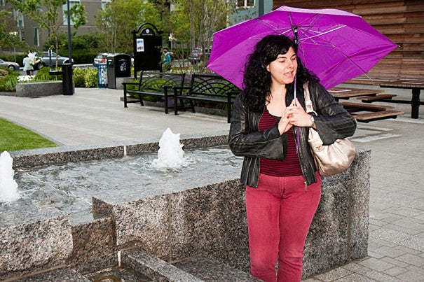 Cambridge resident Ajda Snyder takes in the fountain in the rain during the dedication of the Riverside Community Park.