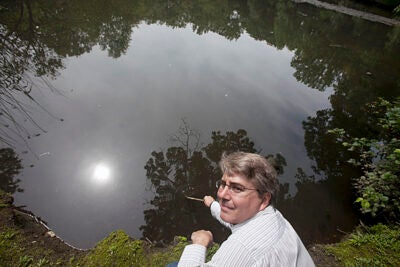 James Shine, Harvard senior lecturer on aquatic chemistry, shows what pollution has done to Boston's Muddy River.