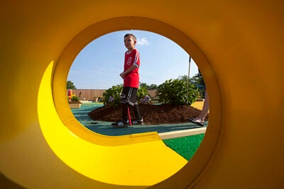 Brighton resident Wyatt Marden, 8, plays miniature golf during the opening of the Harvard Allston Field and Fairway, Harvard's seasonal community facility that also features batting cages.