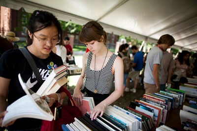 At a recycling exchange under a tent in front of Harvard's Science Center,  Rosalind He (left) and Grace Imeson pore over stacks of free books.